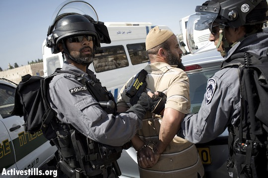 Israeli policemen arrest a Palestinian man after tasing him in the East Jerusalem neighborhood of Ras al Amud, September 27, 2013. Israeli police closed off prayer to Palestinian worshipers under the age if 50 in the Al-Aqsa Mosque, forcing Palestinians to pray in different locations outside of checkpoints. (Activestills)