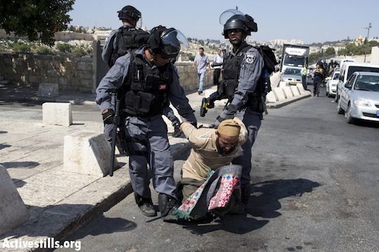 Israeli policemen arrest a Palestinian man after shooting him with a Taser gun in the East Jerusalem neighborhood of Ras al Amud, September 27, 2013. Israeli police prevented Palestinian worshipers under the age if 50 to enter the Al-Aqsa Mosque, forcing Palestinians to pray in different locations near checkpoints. Clashes erupted in different neighborhoods in East Jerusalem. (photo: Activestills)