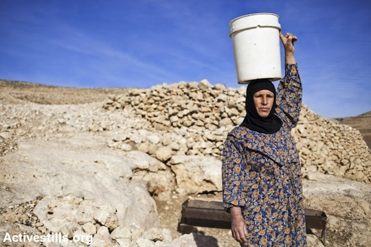 A Palestinian woman carries a bucket of water. (photo: Activestills)