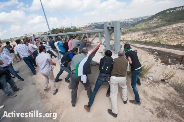 PHOTOS: Palestinian activists dismantle Israeli roadblock