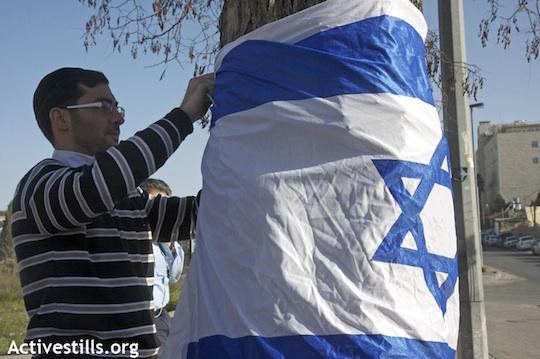 A Jewish settler attaches an Israeli flag to a tree in the East Jerusalem neighborhood of Sheikh Jarrah, January 29, 2010 (Anne Paq/Activestills.org)