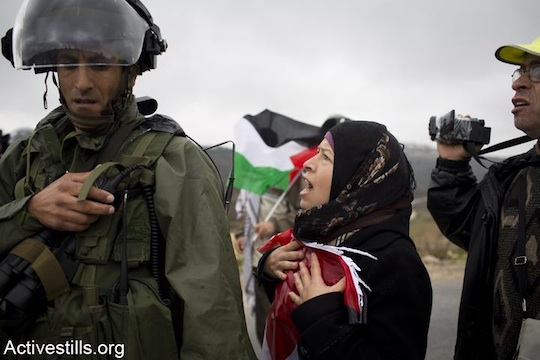 Nariman Tamimi, wife of Bassem Tamimi and sister of Rushdi Tamimi, who was killed by the Israeli army a week before this picture was taken, shouts at a border policeman during the weekly protest against the occupation in the West Bank village of Nabi Saleh, November 23, 2012. (Photo: Oren Ziv/Activestills.org)