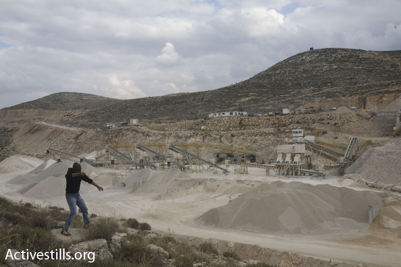A Palestinian youth throwS stones towards an Israeli quarry, built on Palestinian land, during a protest against the separation barrier in the West Bank village of Suqba, on December 11, 2009. (Photo by: Oren Ziv/ Activestills.org)