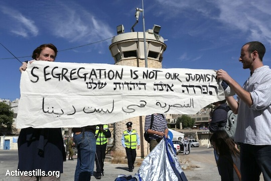 Activists hold a sign reading 'Segregation is not our Judaism,in Hebron , October 25, 2013. (Oren Ziv/Activestills.org)