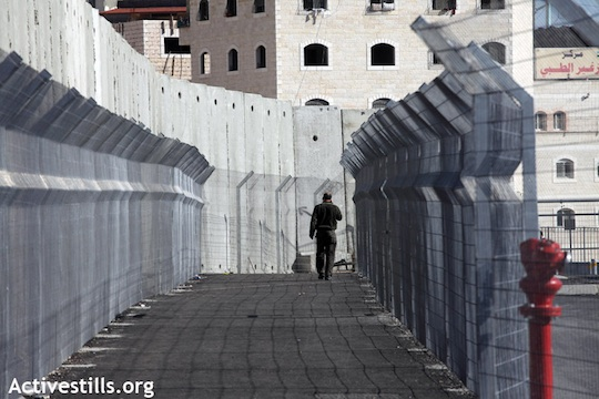 A man walks toward the checkpoint at the entrance of Shuafat Refugee Camp in East Jerusalem, December 27, 2011 (Anne Paq/Activestills.org)