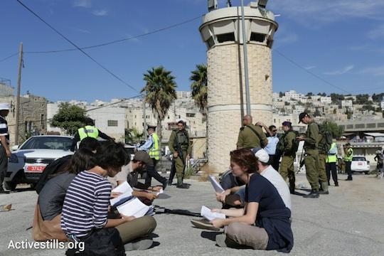 All That's Left activists study the Chayei Sarah Torah portion on Shuhada Street in Hebron, October 25, 2013. (Photo: Oren Ziv/Activestills.org)