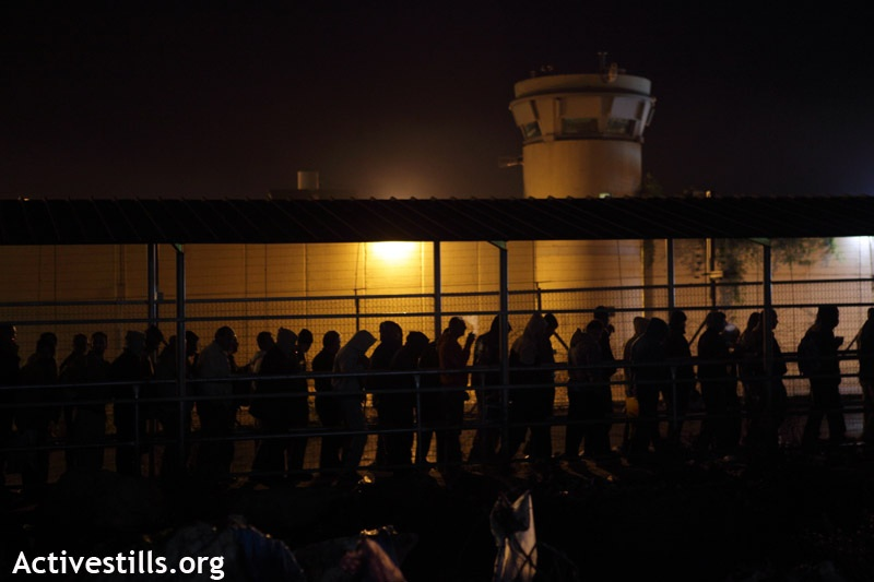 Palestinians workers walk next to the Wall and an Israeli military tower to cross very early the Eyal Israeli military checkpoint into Israel in order to reach their workplace, Qalqiliya, West Bank, 22.11.2011. Thousands of Palestinians are passing this checkpoint every morning, some coming as early as 4am. (Photo by: Anne Paq/Activestills.org)
