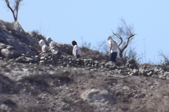 Masked settlers are seen descending from Yitzhar toward Palestinian olive growers on the lands of Burin, October 20, 2013. (Photo: Munir Qadus / Yesh Din)