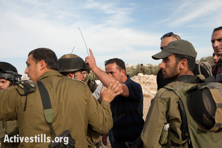 A Palestinian man confronts Israeli soldiers after Israeli civilians under army escort destroyed and damaged olive trees in the West Bank village of Tuqu', November 25, 2013. (photo: Ryan Rodrick Beiler/Activestills.org)