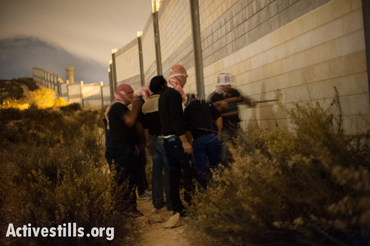 PHOTOS: Palestinians smash hole in the West Bank separation wall