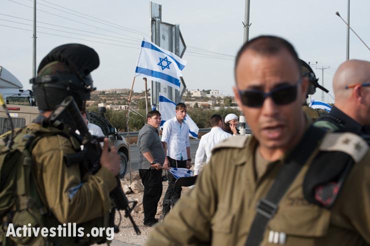 Israeli soldiers protect settler activists demontrating near the West Bank village of Tuqu', November 25, 2013. (photo: Ryan Rodrick Beiler/Activestills.org)