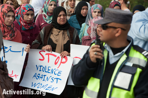 Women from the West Bank town of Bethlehem march past Palestinian Authority policemen during a protest against honor killings and other forms of violence against women, November 16, 2013. (photo: Ryan Rodrick Beiler/Activestills.org)