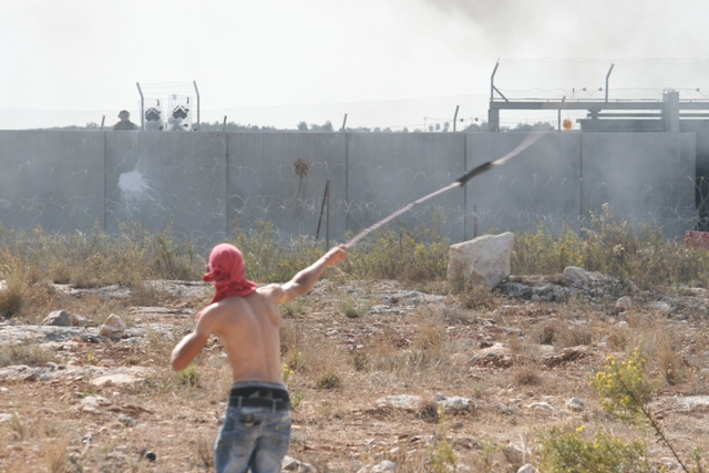 Youth throwing a stone at soldiers behind the wall in Bil'in. (Photo: Haggai Matar)