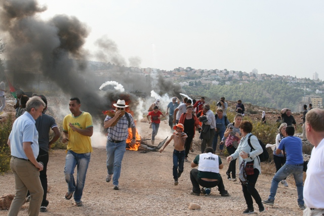 Activists retreating as tear gas is fired into the demonstration (Haggai Matar)