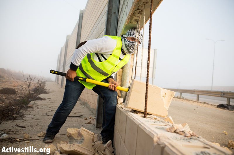 Palestinians manage to break through the separation wall in the West Bank village of Bir Nabala. (photo: Activestills)