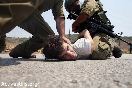 Israeli soldiers hold down an Israeli activist during a demonstration in the West Bank village of Nabi Saleh. (photo: Activestills)