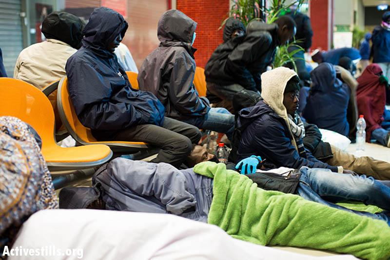 Sudanese refugees who left the 'Holot' open prison camp rest at the Be'er Sheva central bus station, December 15, 2013. (Photo: Activestills.org)