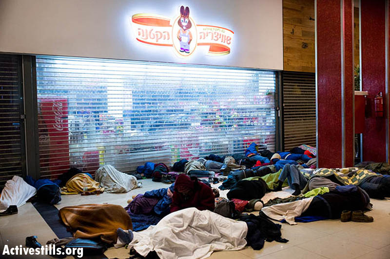 Sudanese refugees who left the 'Holot' detention facility sleep on the ground at the Be'er Sheva central bus station, December 15, 2013. Temperatures were expected to near freezing overnight. (Photo: Activestills.org)