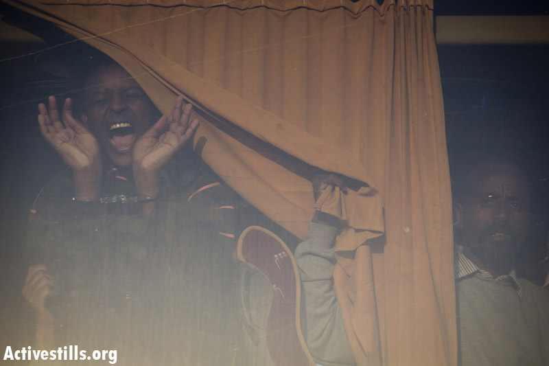An African asylum seeker shouting after being arrested and boarded on a bus taking him back to Holot detention center, after the second March For Freedom, Negev, December 19, 2013. (Activestills.org)