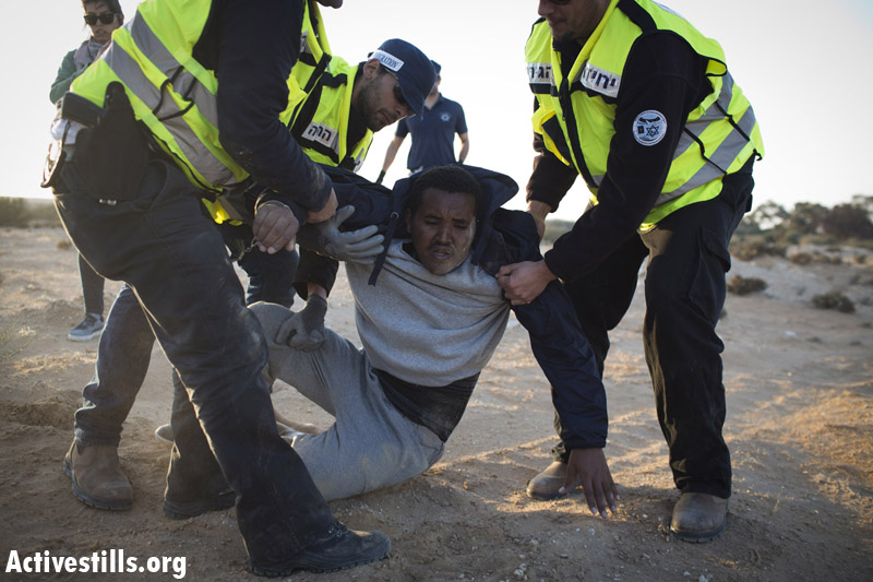 An African asylum seeker is arrested after marching during a second March For Freedom, from the Holot detention center towards Be'er Sheva, Negev, December 19, 2013. (Activestills.org)