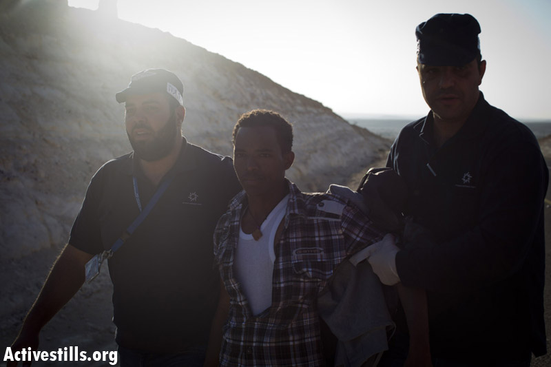 An African asylum seeker is arrested after marching during a second March For Freedom from the Holot detention center towards Be'er Sheva, Negev, December 19, 2013. (Activestills.org)