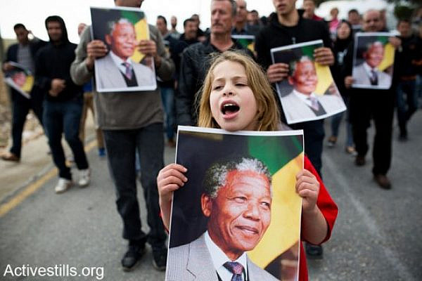 A protester holding a poster with Nelson Mandela's portrait, during a demonstration in the West Bank village of Nabi Saleh, December 7, 2013. The demonstration marked four years to the Popular Struggle in Nabi Saleh,whilecommemorating the killing of Mustafa Tamimi and Rushdi Tamimi by Israeli army forces, and twenty six years since the first Intifada.