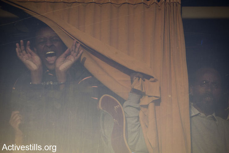 An handcuffed African asylum seeker shouts as he sits inside a police bus, after he was arrested by the immigration police during a Solidarity March For Freedom, Negev, Israel, December 19, 2013. The march set out from Holot detention centre aimed to reach the Southern city of Beer Sheva, and to show solidarity with the March For Freedom arrestees, demanding freedom and recognition of refugee rights. Israeli immigration officers arrested a hundred of them and they were sent back to prison. (Activestills.org)
