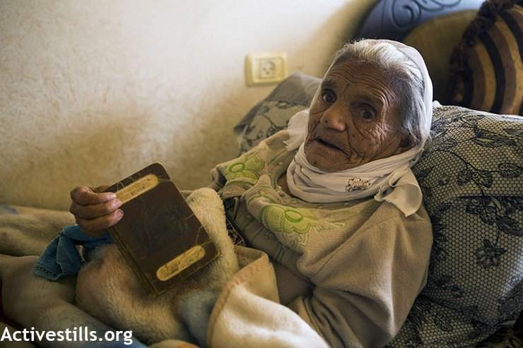 Absiya Jafari, who is more than 100 years old, holds a Palestinian passport issued during the British Mandate, Al Walaja, West Bank, November 23, 2013. The original village of Al Walaja was completely destroyed in 1948 during the Nakba and all villagers were forced to leave and became refugees. (photo: Anne Paq/Activestills.org)