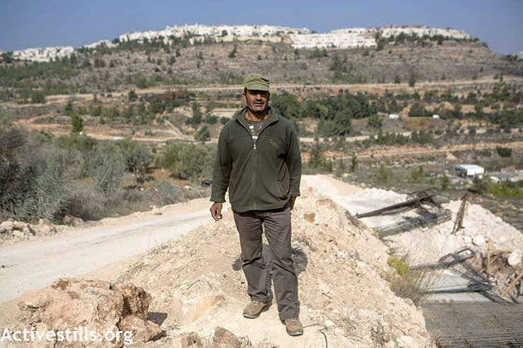 Hisham Abu Ali stands next to new concrete foundations and road construction that willdestroy 50 of his olive trees in Al Walaja village, West Bank, November 12, 2013.(photo: Anne Paq/Activestills.org)