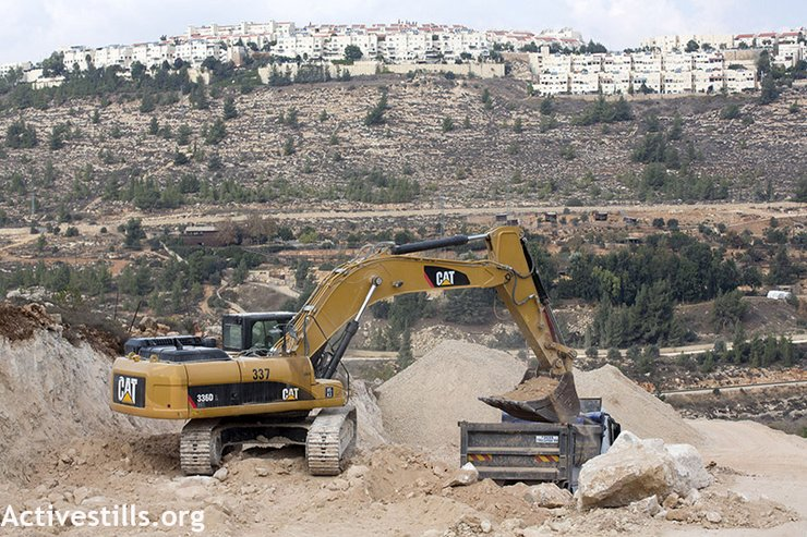The Israeli settlement Gilo, illegal under international law, covers a nearby hillside as construction on a road ostensibly connecting the Cremisan Monastery to Jerusalem threatens to uproot olive trees belonging to Hisham Abu Ali and other residents of Al Walaja, West Bank. (photo: Anne Paq/Activestills.org)