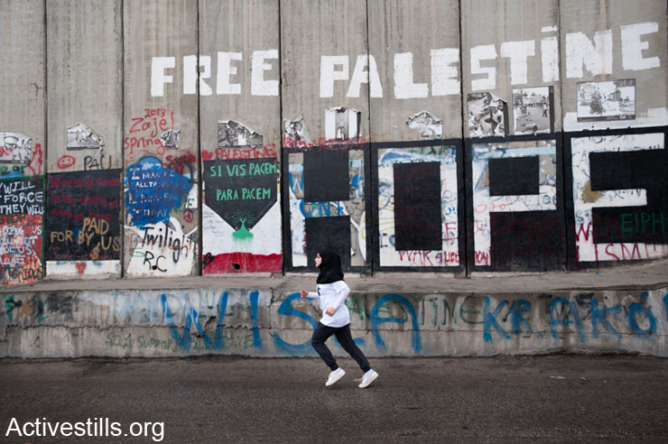 """A young woman runs past the slogans """"Free Palestine"""" and """"Hope"""" painted on the Israeli separation wall as hundreds of Palestinian and international athletes took part in the the inaugural Palestine Marathon in Bethlehem, West Bank, April 21, 2013. (Activestills)"""
