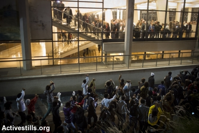 Asylum seekers marching under a crown of classical music lovers at Tel Aviv's Culture Palace (Oren Ziv / Activestills)