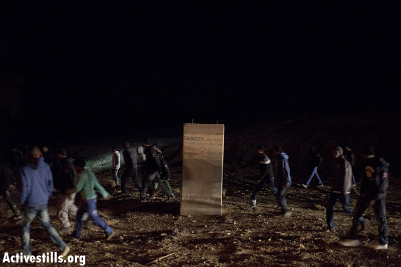 African asylum seekers run away from immigration police, after taking part in the second March For Freedom from the Holot detention center towards Be'er Sheva, Negev, December 19, 2013. (Activestills.org)