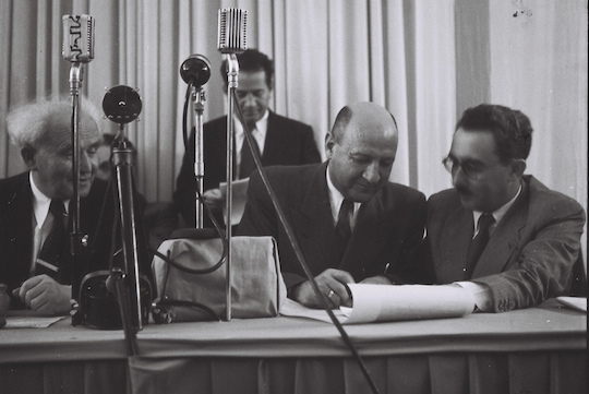 Eliezer Kaplan, with Moshe Shertok and David Ben-Gurion looking on and Zeev Sharef standing behind them, sign the Declaration of Independence at the Museum in Tel Aviv. (Zoltan Kluger/GPO)