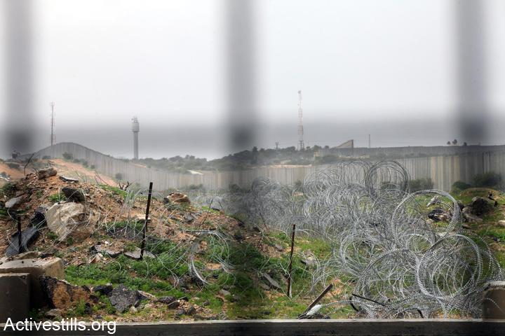 Barbed wire, and behind that the border wall can be seen through the fence at Erez Crossing terminal, the northern checkpoint leading from the Gaza Strip to Israel. (Anne Paq/Activestills.org)