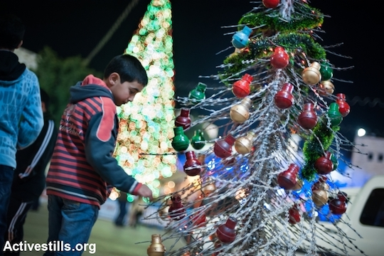A Christmas tree made of razor wire and tear gas grenades is displayed in Manger Square, Bethlehem as part of an activist art exhibit, December 21, 2013. (Ryan Rodrick Beiler/Activestills.org)