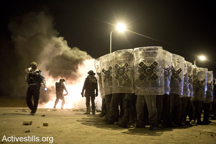 """Israeli policemen advance as Bedouin youth throw stones during a protest against the Israeli government's Prawer Plan, on road 31 on November 30, 2013 near the town of Hura, Israel. Police fired tear gas and arrested at least 10 protesters. Activists protested in the Negev, Haifa, Jerusalem, Ramallah, Gaza and around the world, marking the third """"Day of Rage"""" against the plan."""