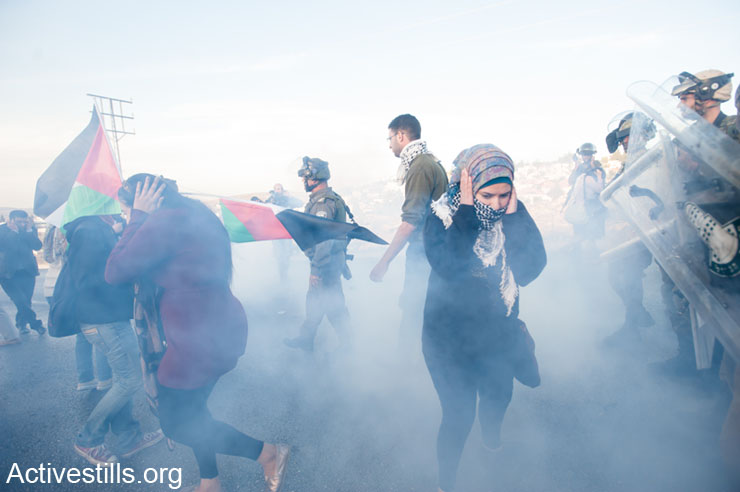 """Palestinian and international activists react to stun grenades thrown by Israeli forces during the """"Day of Rage"""" protest against the Prawer-Begin Plan in front of the Israeli settlement Bet El, Al Jalazun, West Bank, November 30, 2013. Three Palestinians were arrested by Israeli soldiers during the demonstration."""