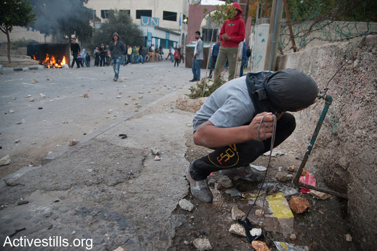 A Palestinian youth drinks from a public water tap during a lull in clashes with Israeli forces in Aida Refugee Camp in the West Bank town of Bethlehem, November 29, 2013. This day's clashes followed several days of confrontations followed the killing of three Palestinian militants by Israeli forces in Yatta.