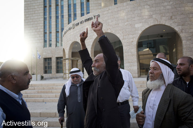 Sheikh Sayah Aturi is welcomed by family members and activists as he walks out from the Be'er Sheva court, following his release from arrest, November 28, 2013. Sayah was arrested on November 20, after his village Al Arakib was demolished by the Israeli authorities. Since then, he remained in jail after refusing to sign an order denying him entrance to his lands. The court decided to release him for a week of house arrest outside his village.