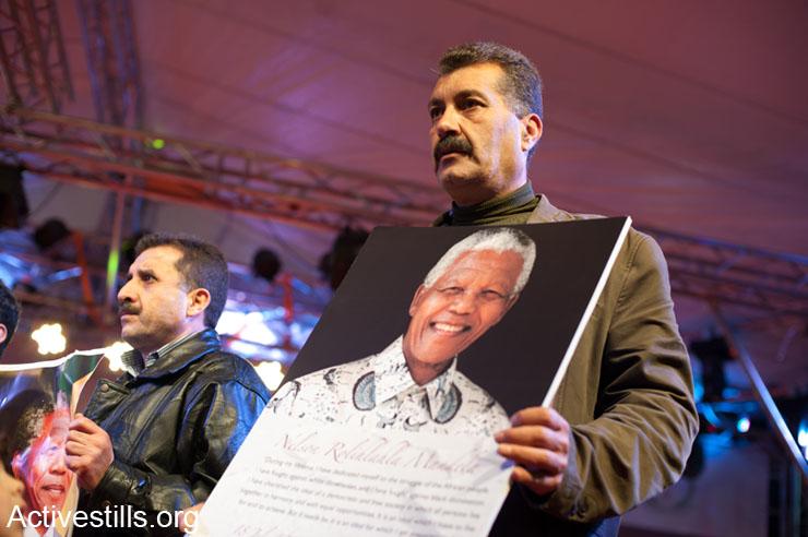 Bethlehem-area activists honor the memory of Nelson Mandela at a ceremony in Manger Square, West Bank, December 7, 2013. (photo: Ryan Rodrick Beiler/Activestills.org)