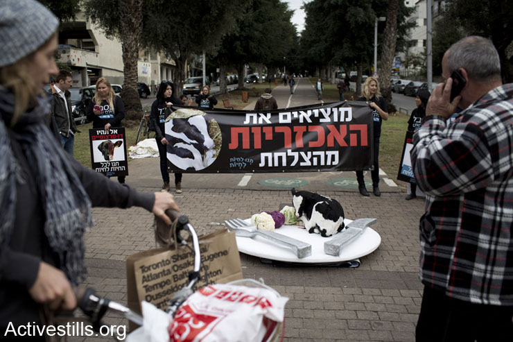 Israeli animal rights activists take part in a vigil against the meat industry, displaying a 1-day-old dead calf on a big plate in center Tel Aviv, December 10, 2013. (photo: Oren Ziv/Activestills.org)