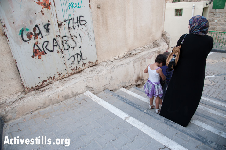 """A Palestinian woman and children pass the slogan """"Gas the Arabs! JDL"""" spray-painted on an exterior wall of the Cordoba School for Palestinian children near Shuhada Street, Hebron, October 22, 2012. """"JDL"""" stands for Jewish Defense League, an extremist group founded by Meir Kahane and designated as a terrorist group by the FBI. Baruch Goldstein was a charter member of the JDL, which has designated him """"a martyr in Judaism's protracted struggle against Arab terrorism."""""""