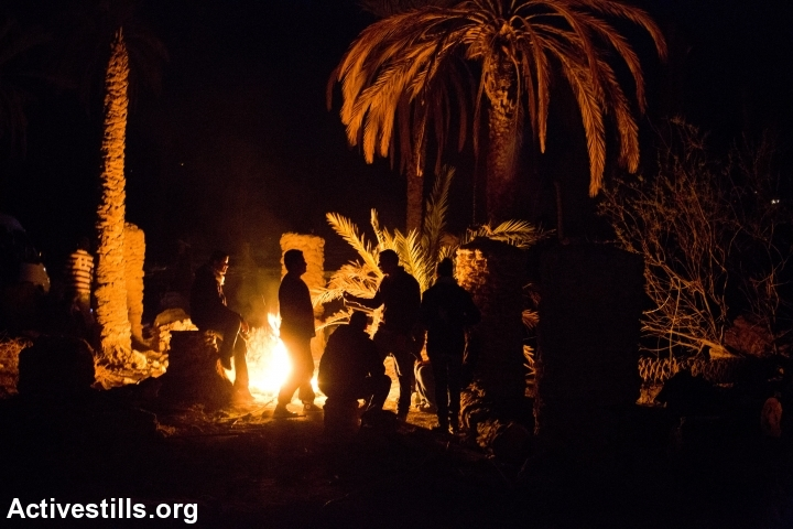 Palestinian activists around a bonfire in Ein Hijleh protest village, in the Jordan Valley, West Bank January 31, 2014.