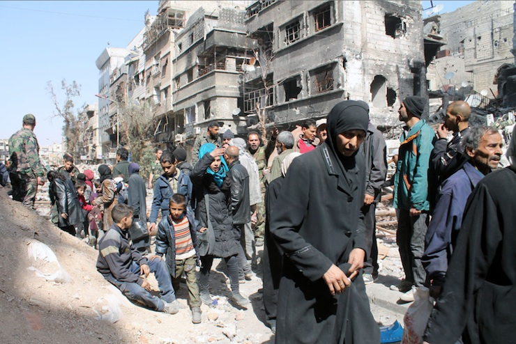 Gathered on Yarmouk Street, residents begin hurrying to reach the distribution point.' (Photo by UNRWA)