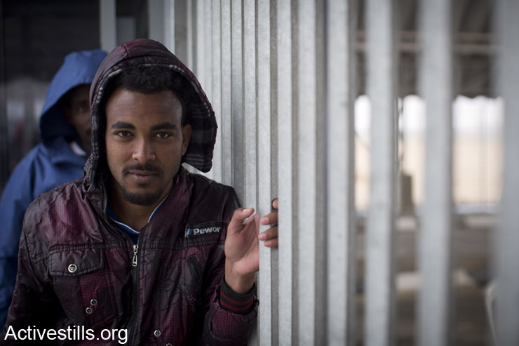 An African asylum seeker jailed in Holot detention center waits to re-enter the facility after meeting activists and friends who came for a solidarity visit, Negev, February 15, 2014. (photo: Oren Ziv/Activestills.org)