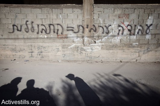 "A ""Price Ta"" graffiti is seen sprayed on the wall of a Palestinian house in the Silwan neighborhood of East Jerusalem, February 10, 2014. The graffiti reads: ""Arab work is assimilation"". (photo: Tali Mayer/Activestills.org)"