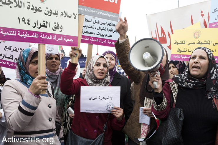 Women shout slogans during the International Women's Day march in Qalandiya, West Bank on March 8th, 2014. Around 400 women and supporters marched to the Israeli checkpoint holding signs and shouting slogans against the occupation, calling to boycott Israel. The demonstration was dispersed by Israeli forces with tear gas and shock grenades.