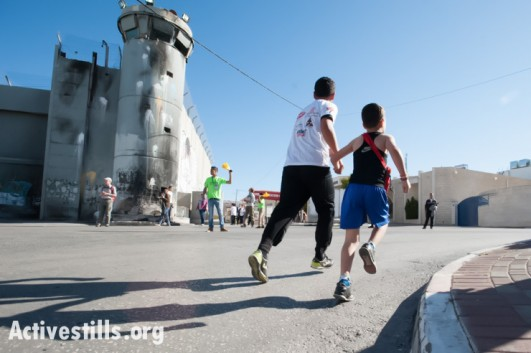 A Palestinian father and son run past the Israeli separation wall dividing the West Bank town of Bethlehem during the second annual Palestine Marathon, April 11, 2014. (photo: Activestills.org)