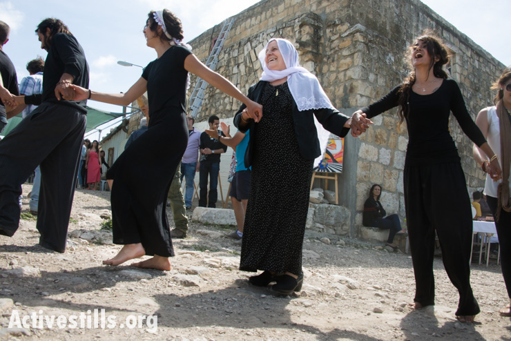 On Easter Monday in the displaced Palestinian village of Iqrit, young and old dance around the town's church. Northern Israel, April 21, 2014. Iqrit's original inhabitants were forcibly evacuated in the Nakba of 1948. Though the Israeli high court granted the residents, who are Palestinian citizens of Israel, the right to return to their homes in 1951, the military destroyed the village and has since prevented their return. Only the village's church and cemetery remained intact, and are still used by village residents while they campaign for a full return.
